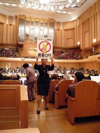 Koncertním sálem procházejí uvaděčky s výstrahou srozumitelnou ve všech světových jazycích. Je těsně před koncertem ve Fukui.